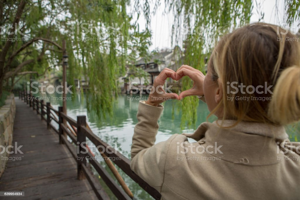 Young woman in Chinese village makes heart shape finger frame stock photo