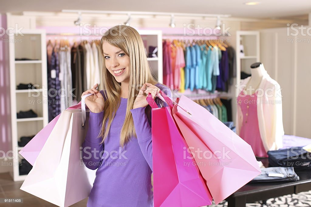 Young woman in clothing store holding shopping bags royalty-free stock photo