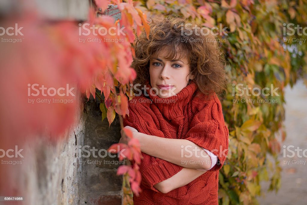 Young woman in colorful leaves feeling cold stock photo