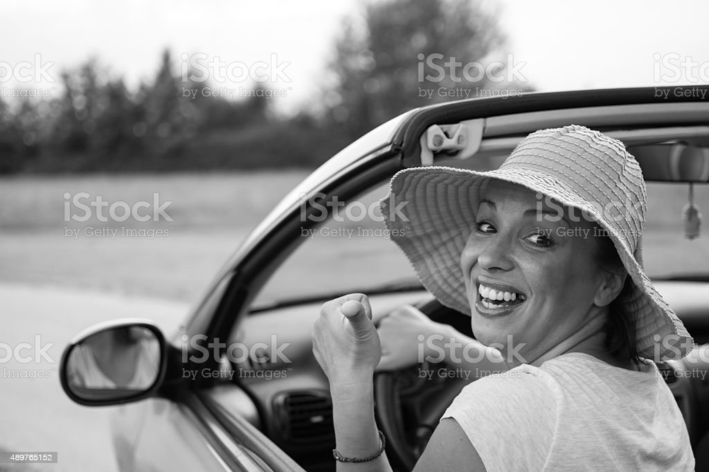 Young woman in convertible with pink hat stock photo