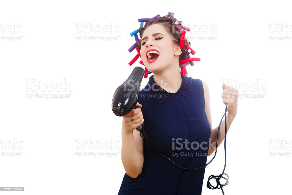Young woman in curler expressively singing. Isolated. stock photo