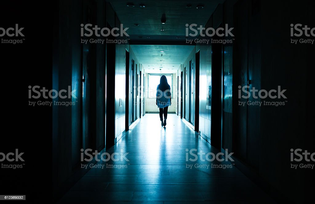 Young woman  in dark building walkway stock photo