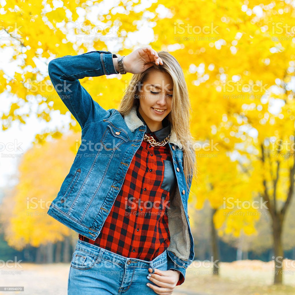 Young woman in denim clothing with autumn leaves stock photo