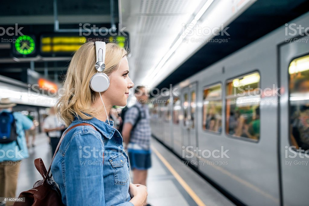Young woman in denim shirt at the underground platform, waiting stock photo