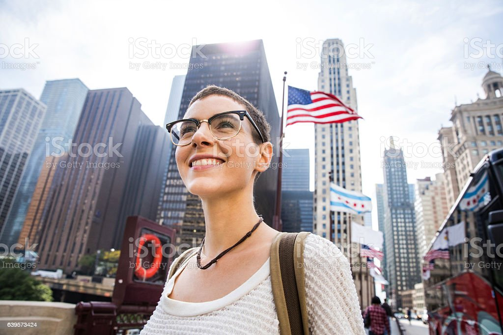 Young woman in downtown Chicago against US flag stock photo