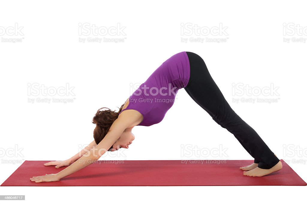 Young woman in Downward Facing Dog Pose stock photo