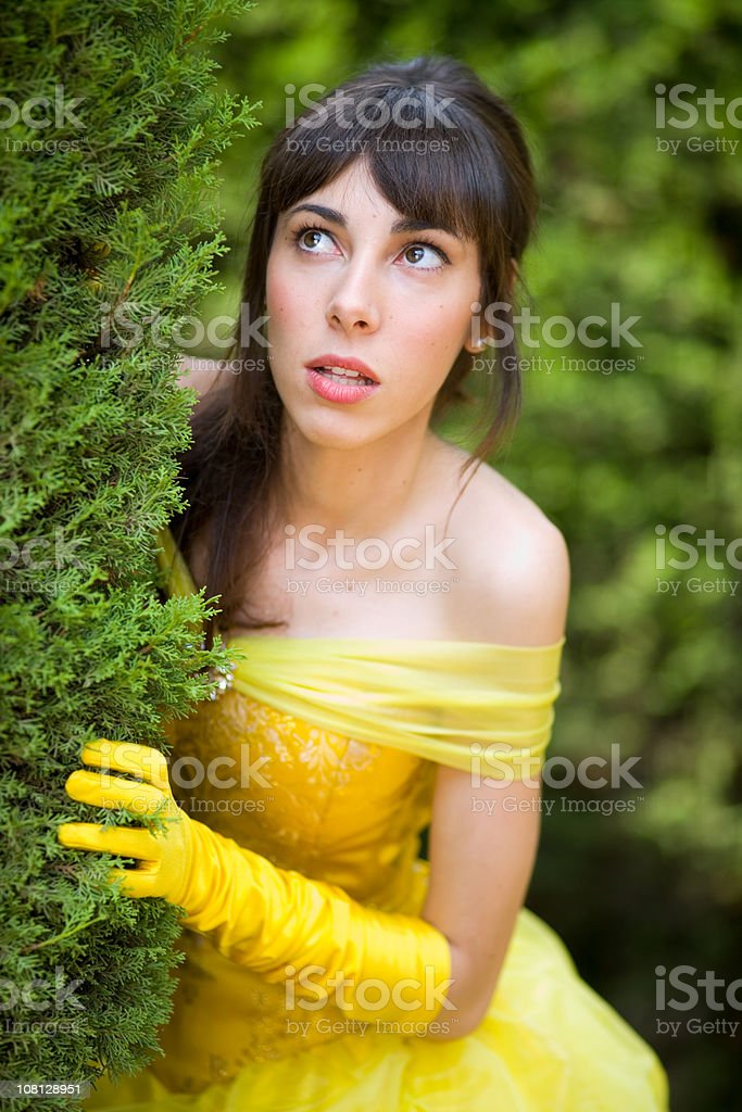 Young Woman in Dress Looking Around Hedge royalty-free stock photo