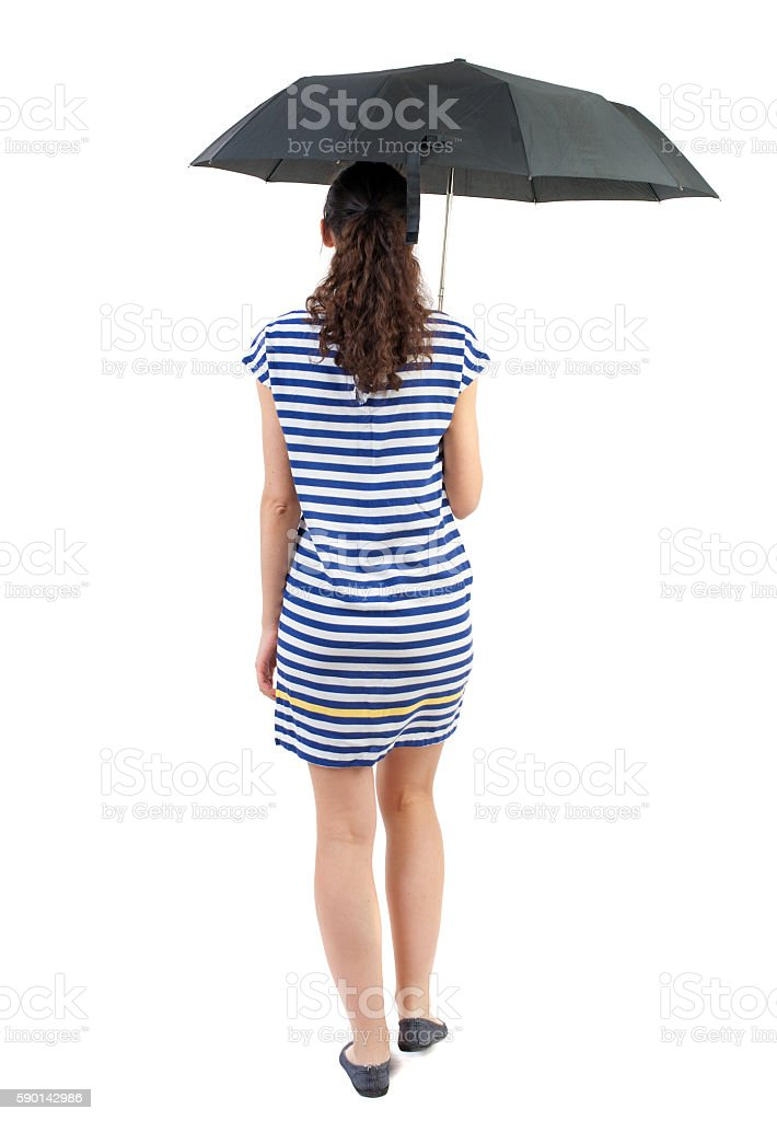 young woman in dress walking under an umbrella. stock photo