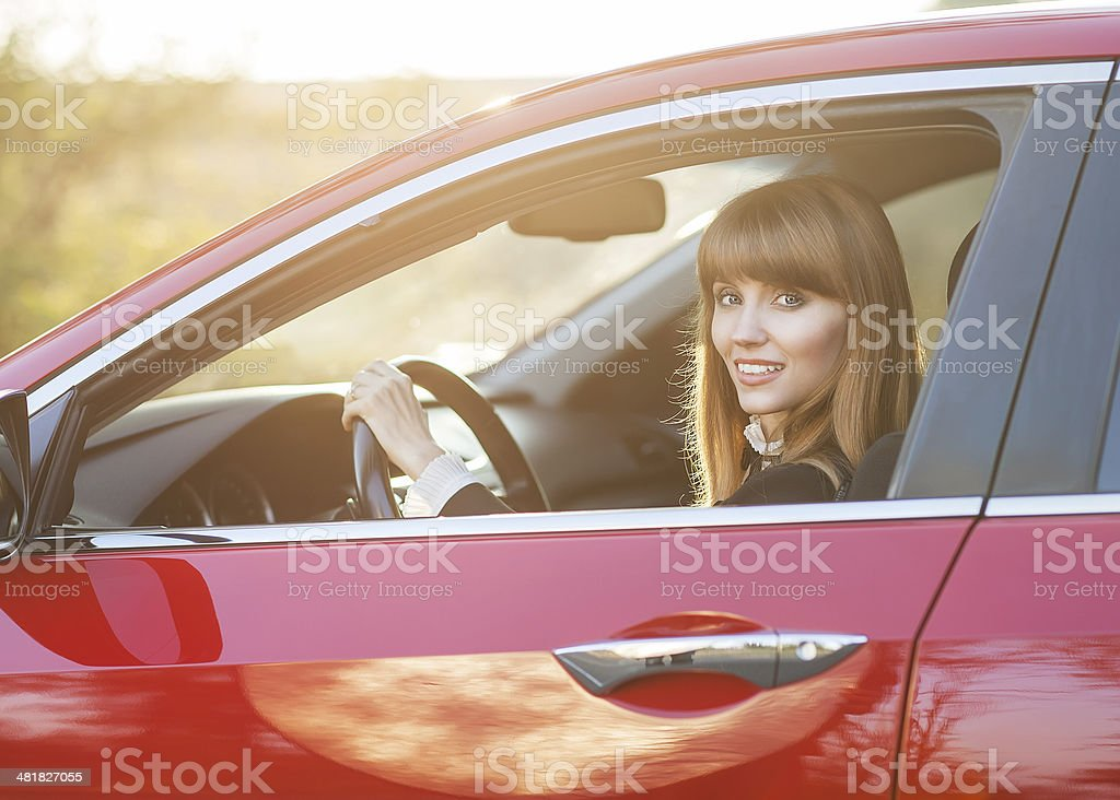 Young woman in drivers seat of a red car at sunset stock photo