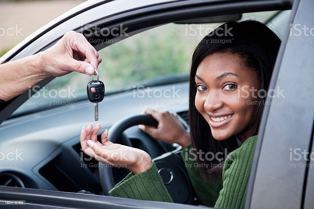 Young woman in driver's seat takes the car key stock photo