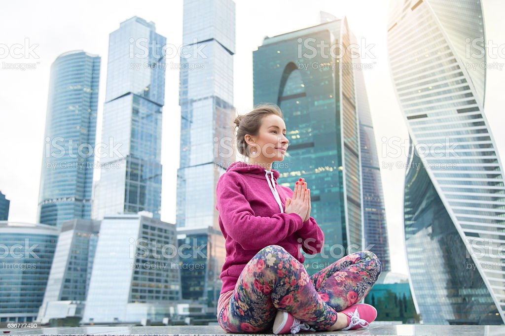 Young woman in Easy Seat pose against the skyscraper stock photo