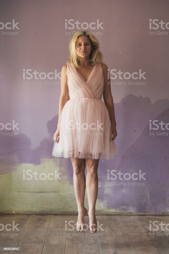 Young woman in elegant costume jumping stock photo