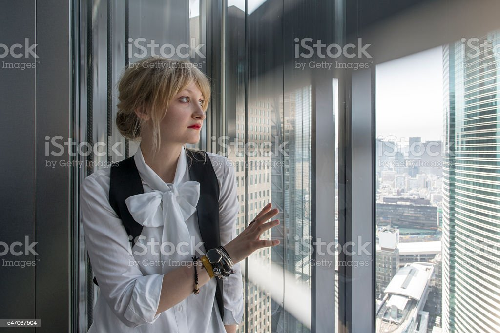 Young woman in elevator watching the view. stock photo