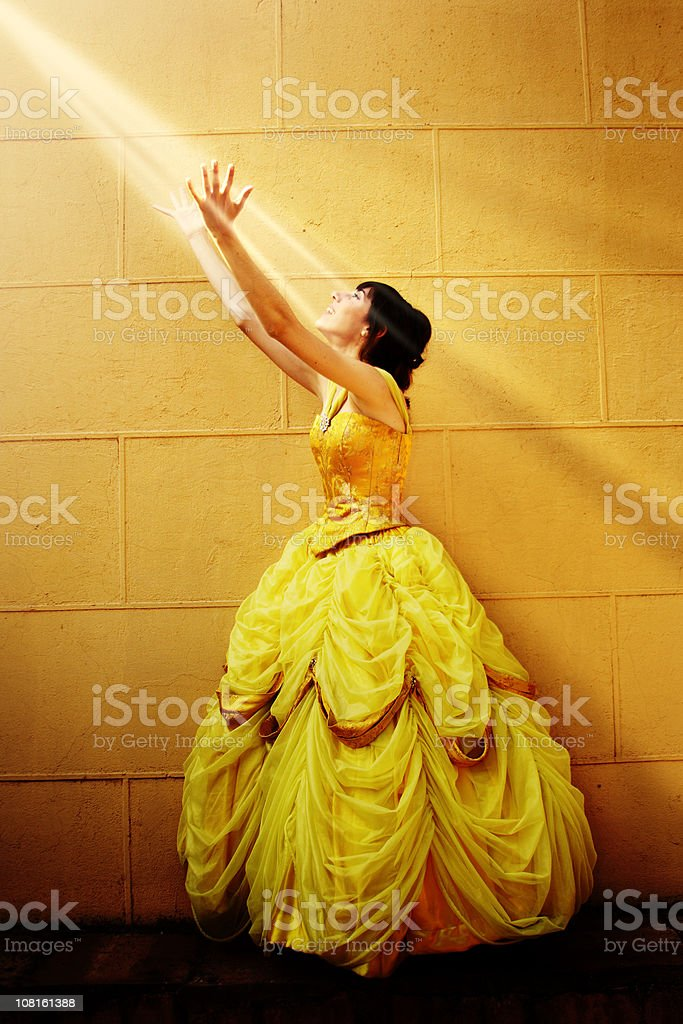 Young Woman in Fancy Dress Reaching Out to Sunlight royalty-free stock photo