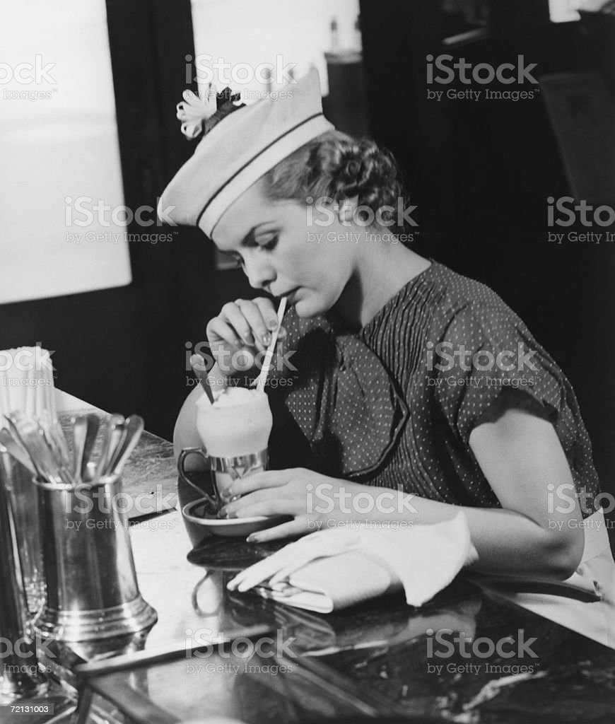 Young woman in fancy hat drinking ice cream soda (B&W) stock photo