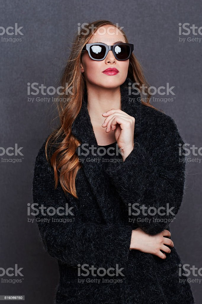 Young woman in fashionable black coat and shades stock photo
