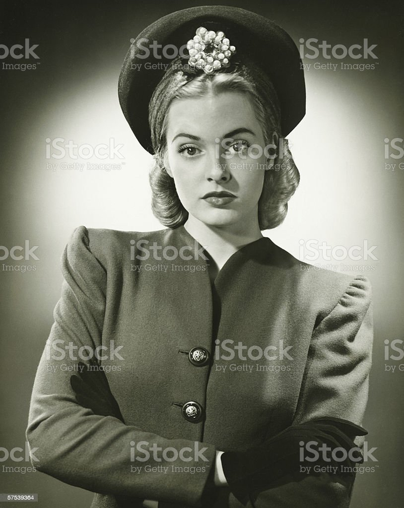 Young woman in fashionable suit and hat in studio, (B&W), portrait royalty-free stock photo