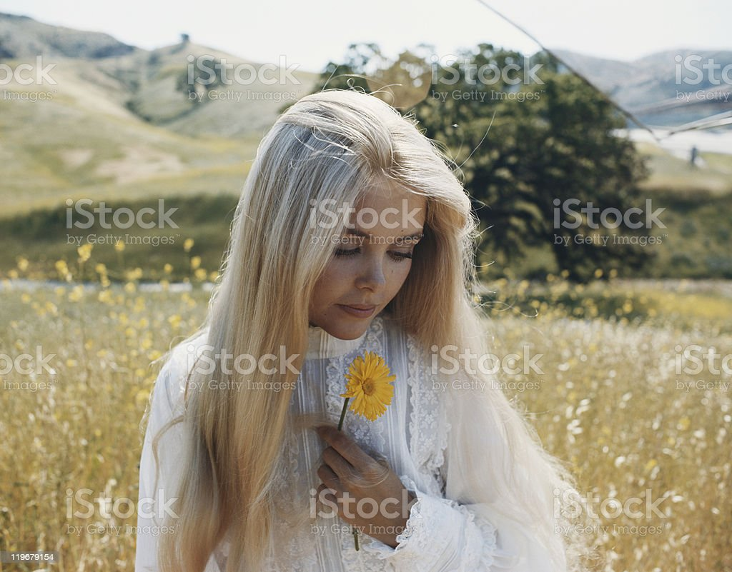 Young woman in field holding flower  royalty-free stock photo