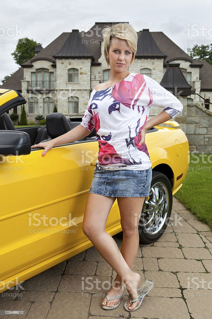 Young woman in front of sports car and mansion stock photo
