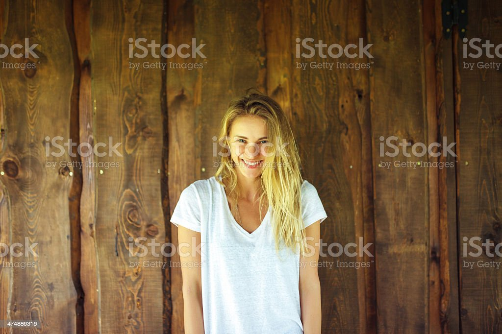 Young woman in front of wooden wall stock photo