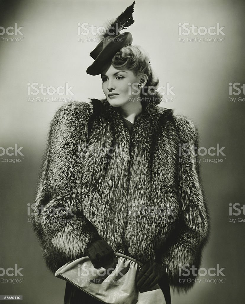 Young woman in fur coat and fashionable hat in studio, (B&W) stock photo