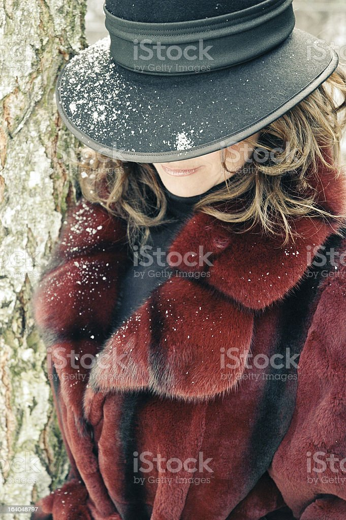 Young woman in fur coat and snowy hat royalty-free stock photo