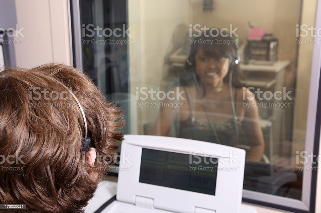 Young woman in glass booth completing a hearing test stock photo