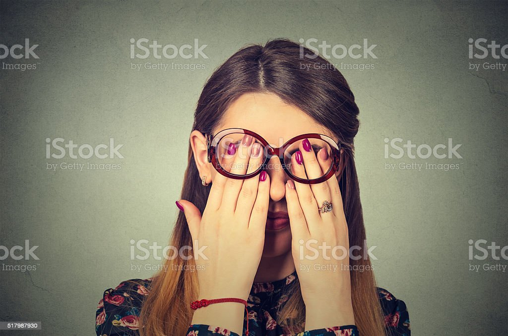 Young woman in glasses covering face eyes with both hands stock photo