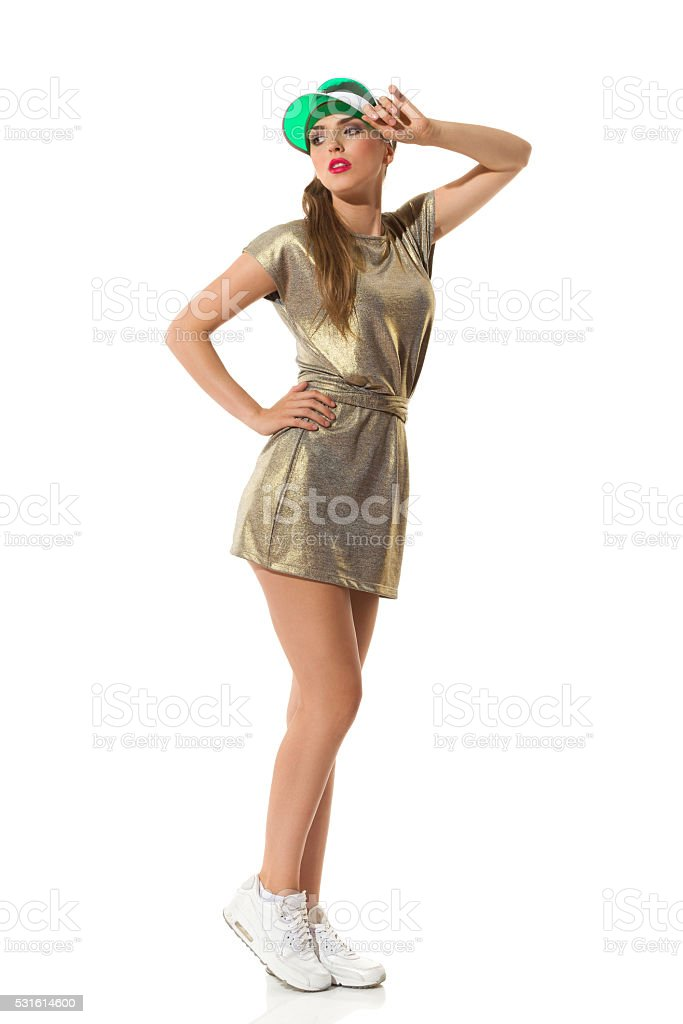 Young Woman In Gold Mini Dress Posing stock photo