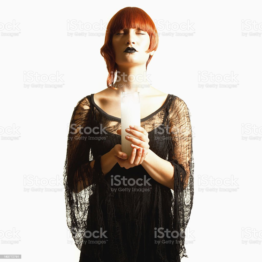 Young Woman in Gothic Attire Holding Candle with Eyes Closed stock photo