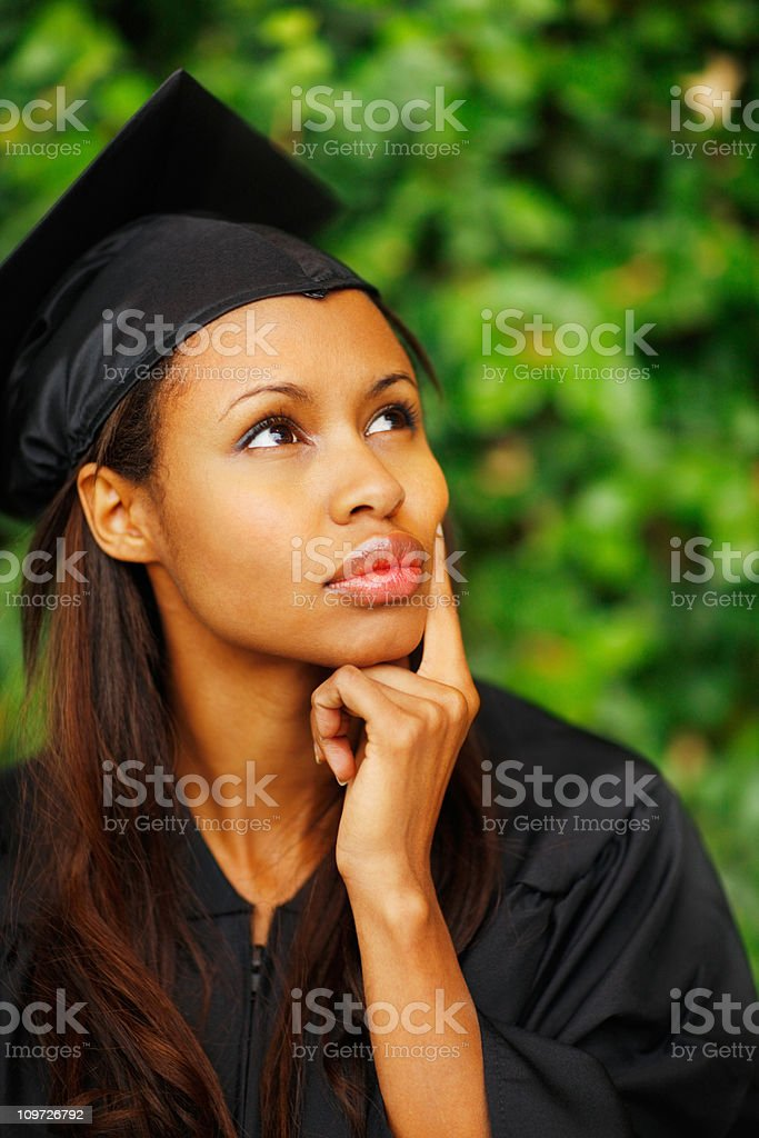 Young woman in graduation gown looking away royalty-free stock photo