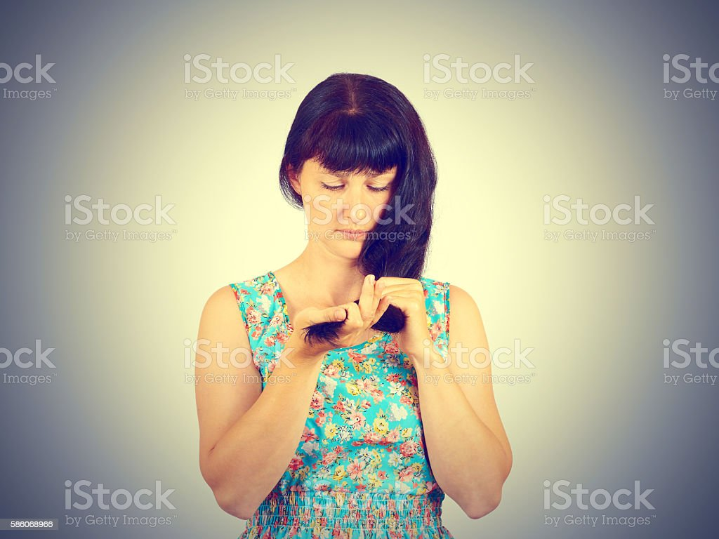 young woman in green dress looks at her problematic hairs. stock photo