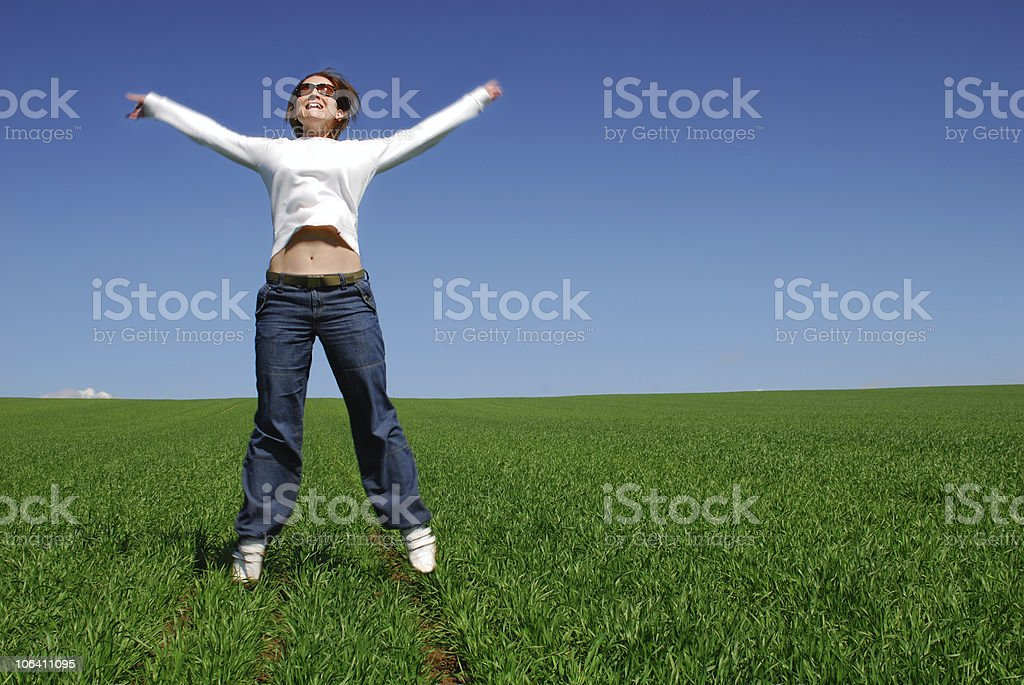 Young woman in green grass arms outstretched royalty-free stock photo