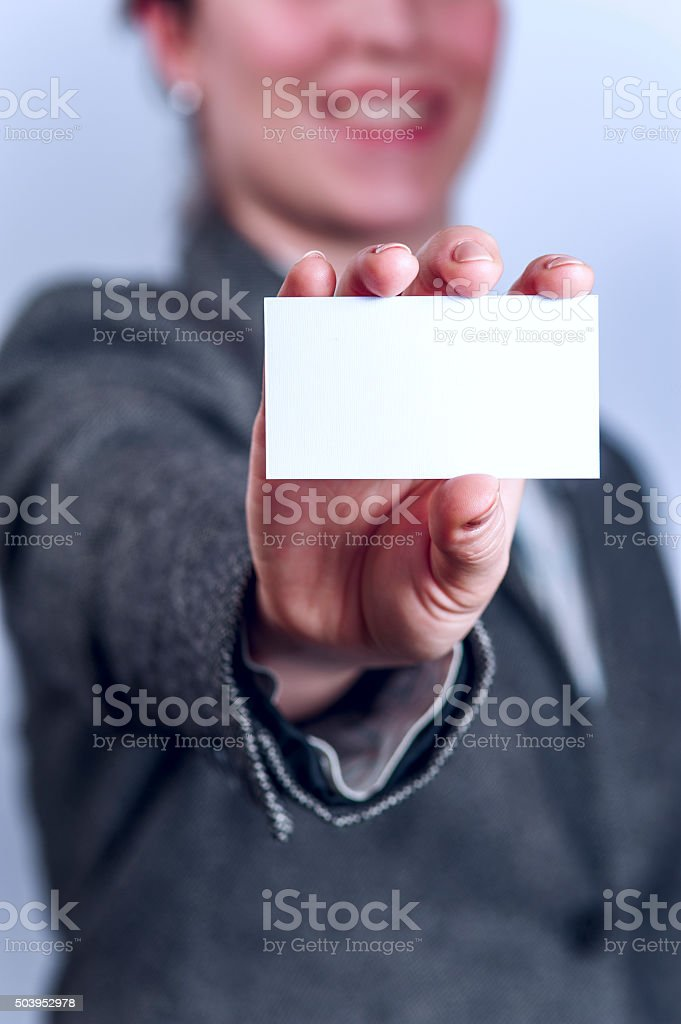 Young woman in grey suit holds business card stock photo