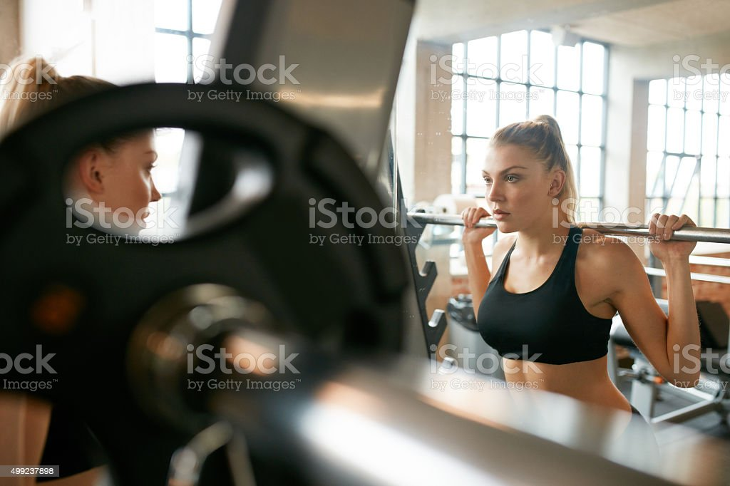 Young woman in gym doing squats stock photo
