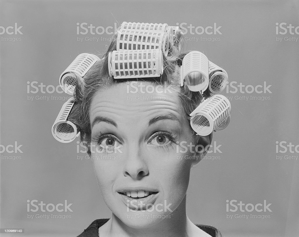 Young woman in hair rollers, smiling, portrait royalty-free stock photo
