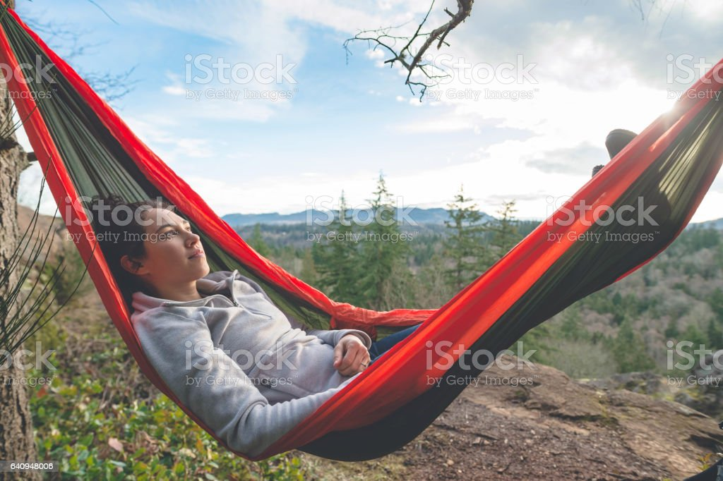 Young woman in hammock in forest stock photo