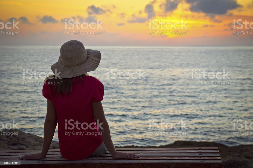 Young woman in hat sitting and looking at sunset royalty-free stock photo