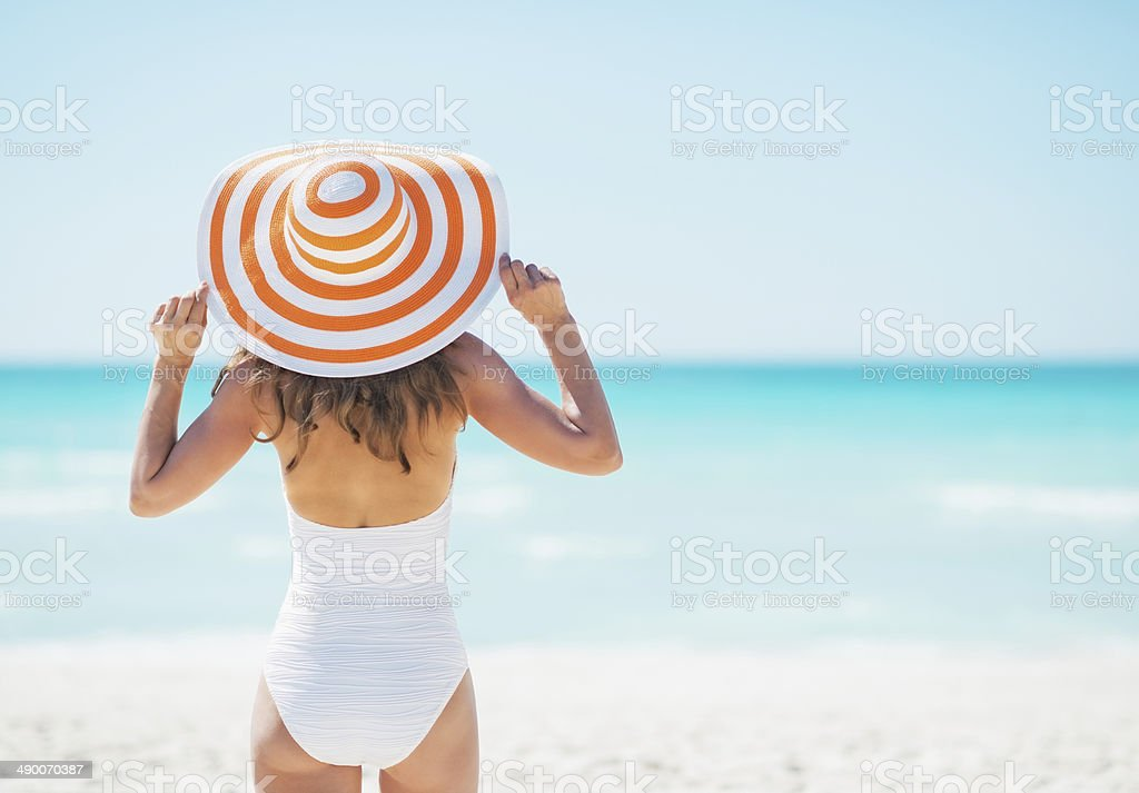 young woman in hat standing on beach. rear view stock photo