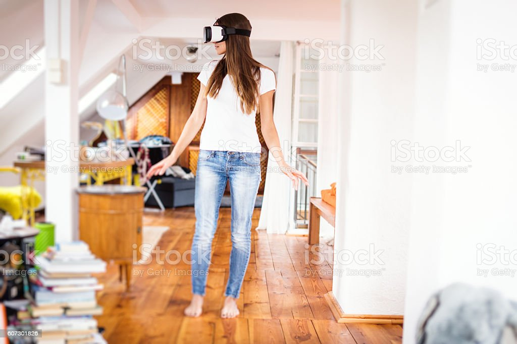 Young woman in her apartment, using VR glasses stock photo