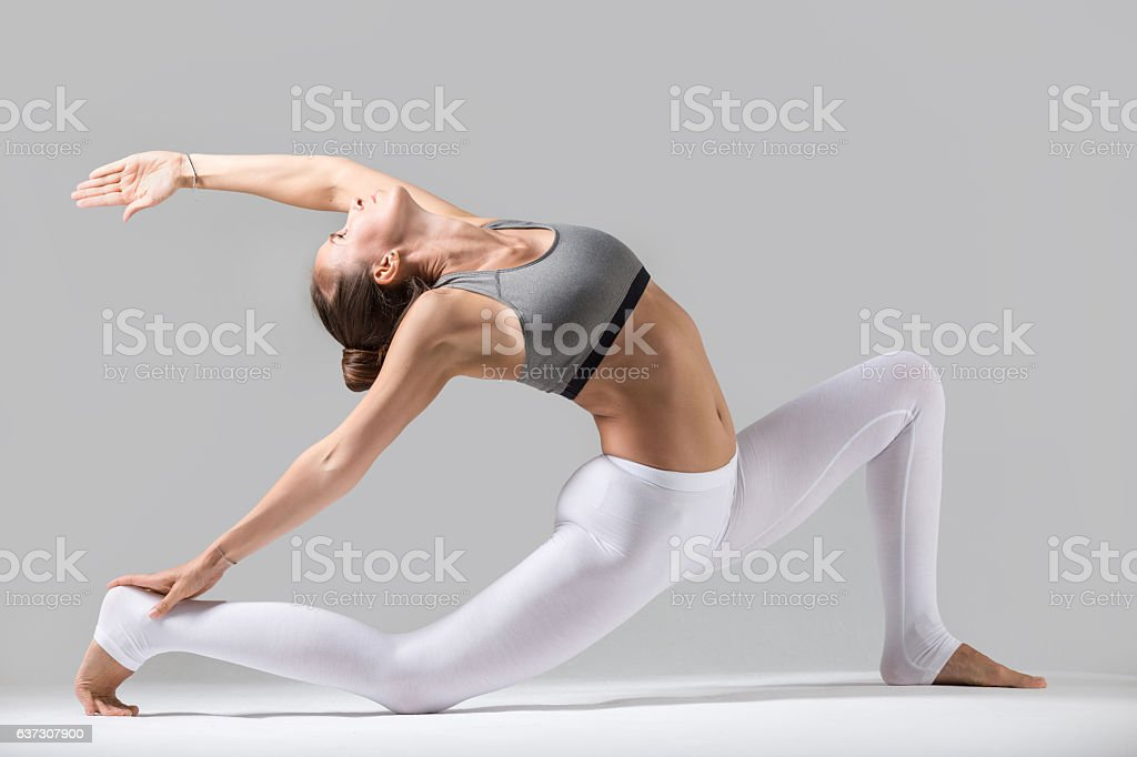 Young woman in Horse rider pose, grey studio background stock photo