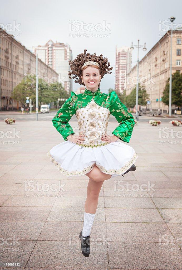 Young woman in irish dance dress and wig dancing stock photo