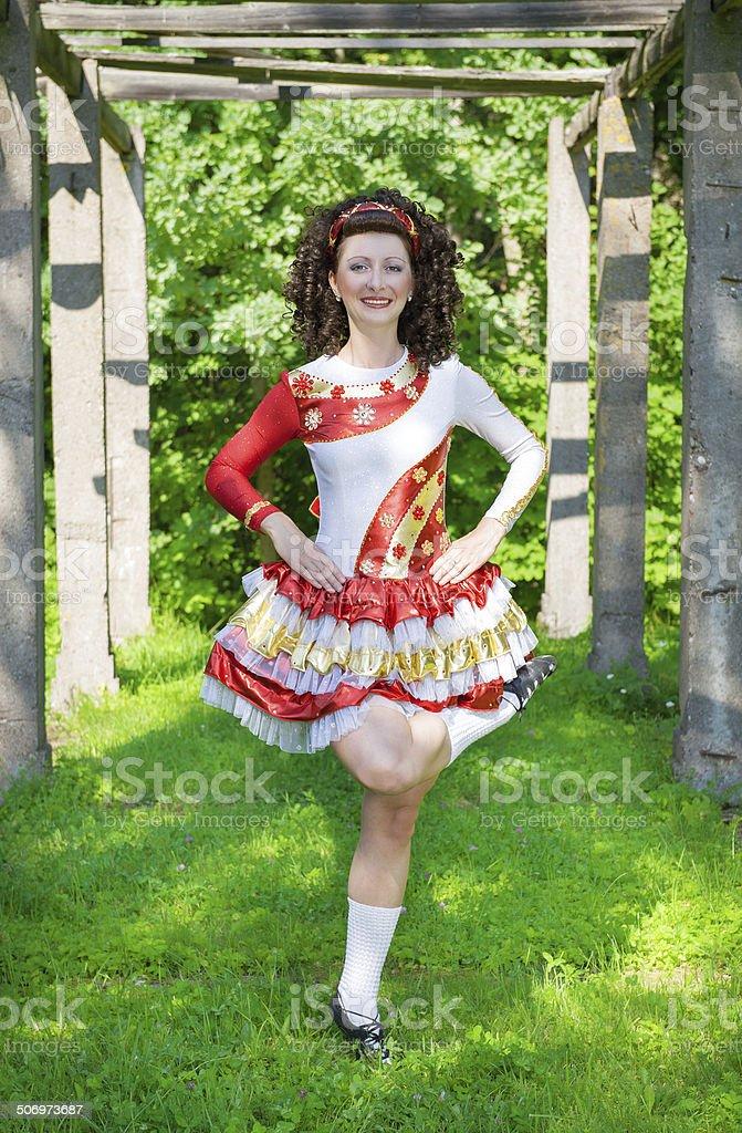 Young woman in irish dance dress dancing outdoor stock photo