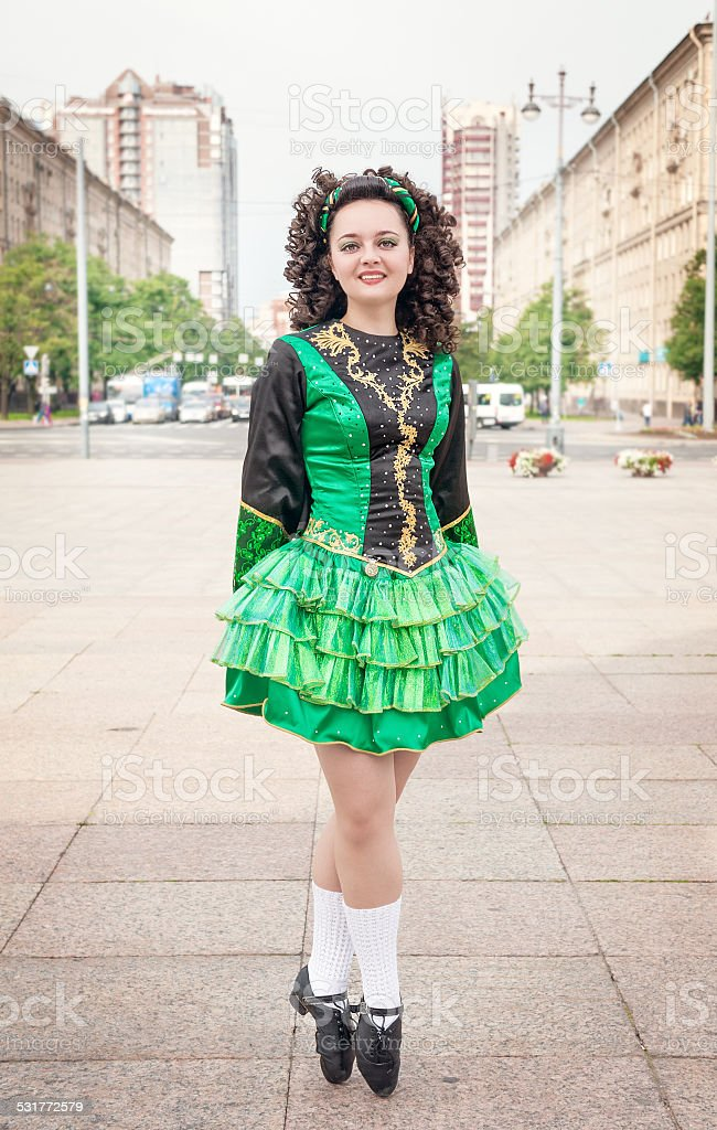 Young woman in irish dance dress posing outdoor stock photo