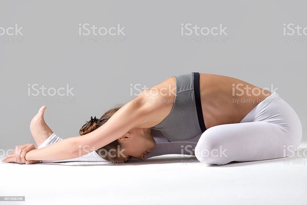 Young woman in Janu Sirsasana pose, grey studio background stock photo