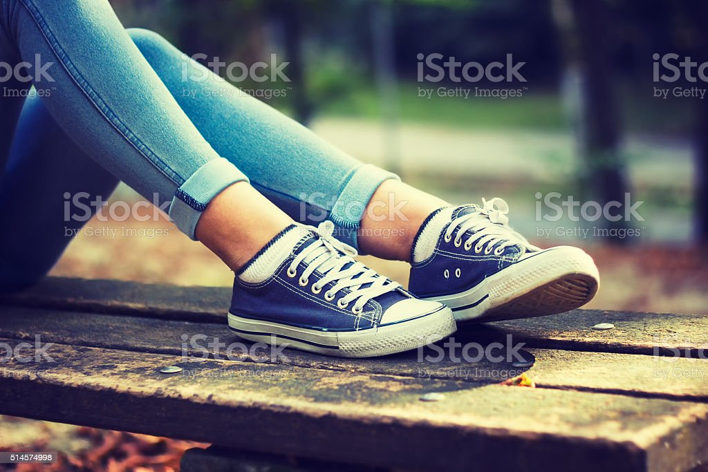 Young woman in jeans and blue sneakers stock photo
