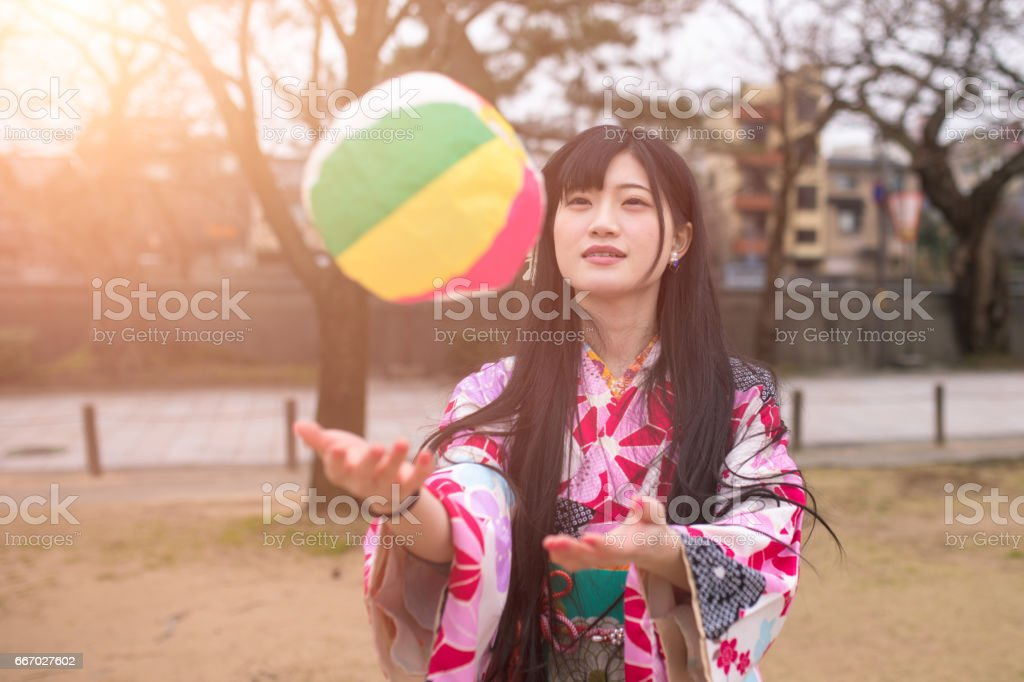 Young woman in Kimono playing traditional Japanese paper balloon stock photo