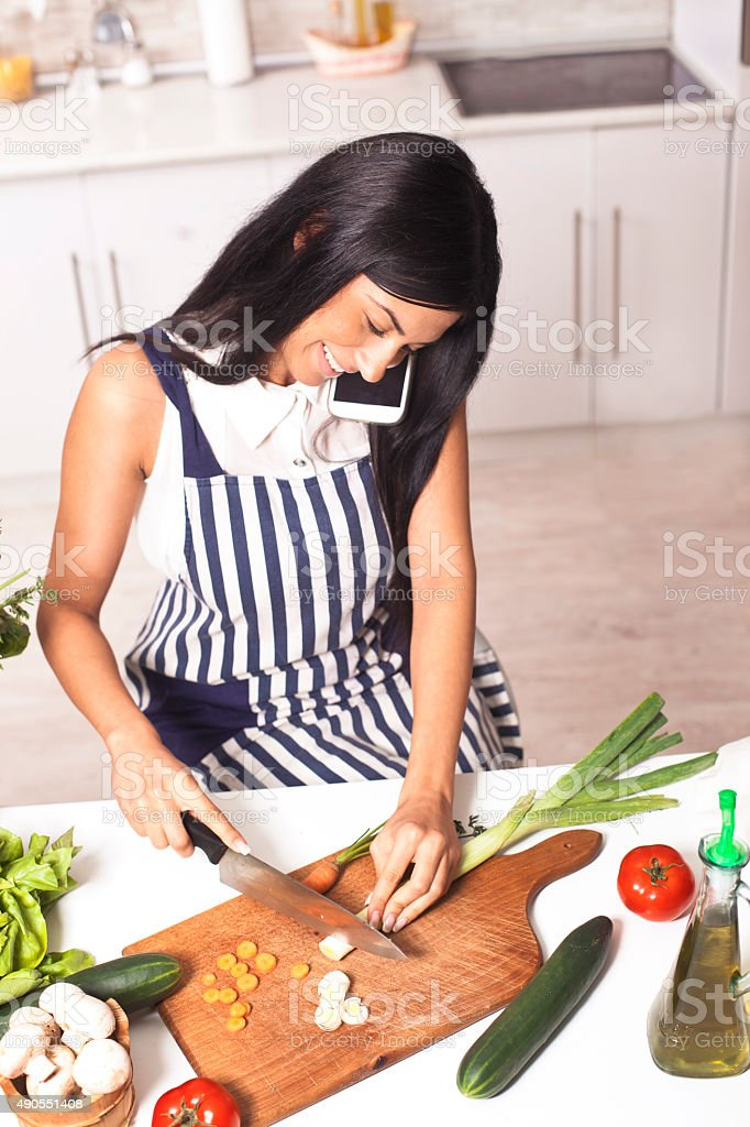 Young  woman in kitchen and talking stock photo