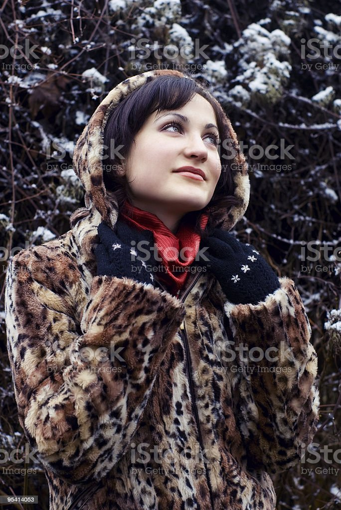 Young woman in leopard fur coat looking up stock photo