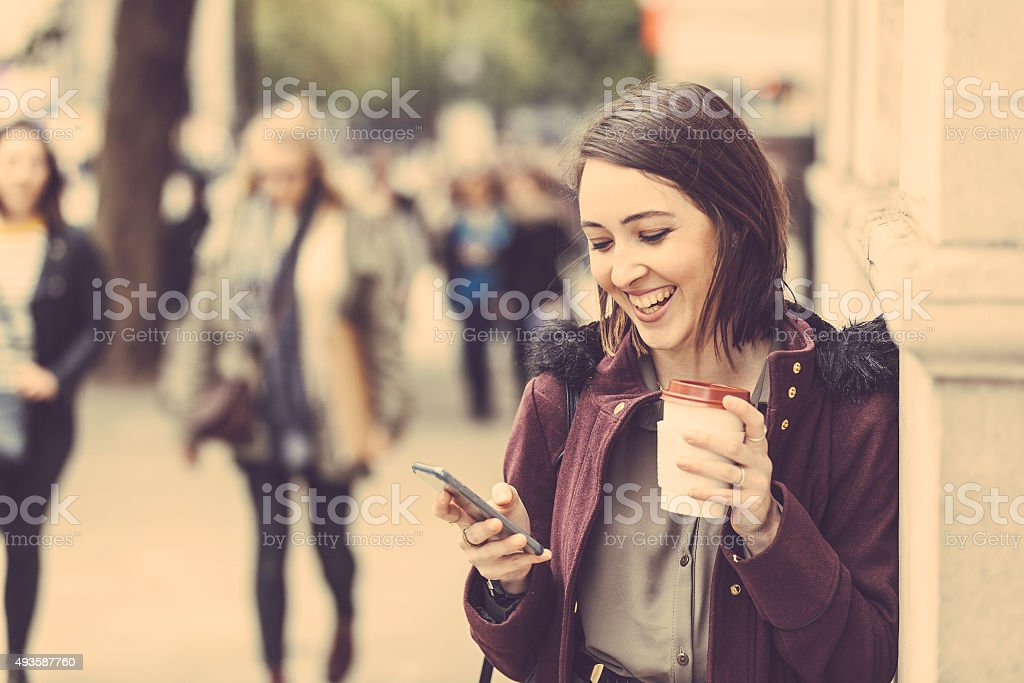 Young woman in London with tea and smart phone stock photo